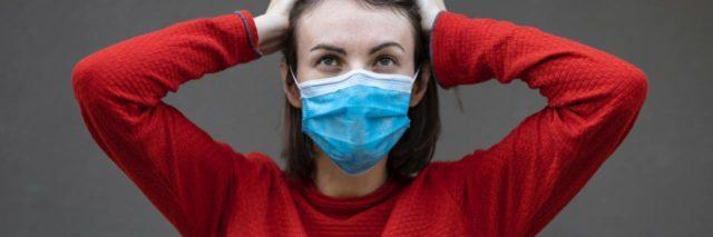 photo of woman in red sweater, wearing blue medical mask, with hands raised to her head