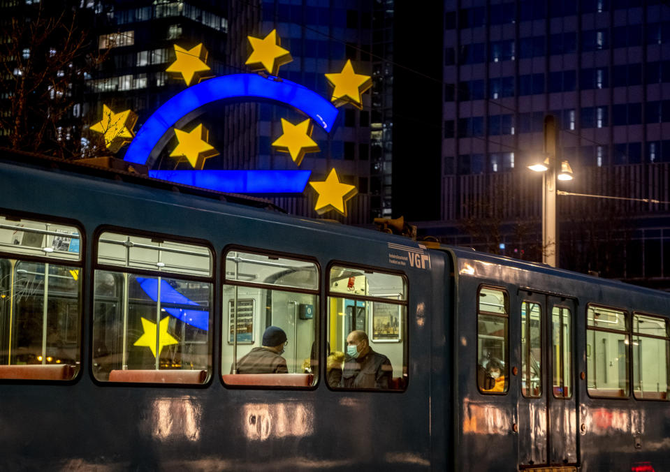 People in a tram pass the Euro sculpture in Frankfurt, Germany, Thursday, March 11, 2021. The European Central Bank will have a meeting of the governing council on Thursday. (AP Photo/Michael Probst)