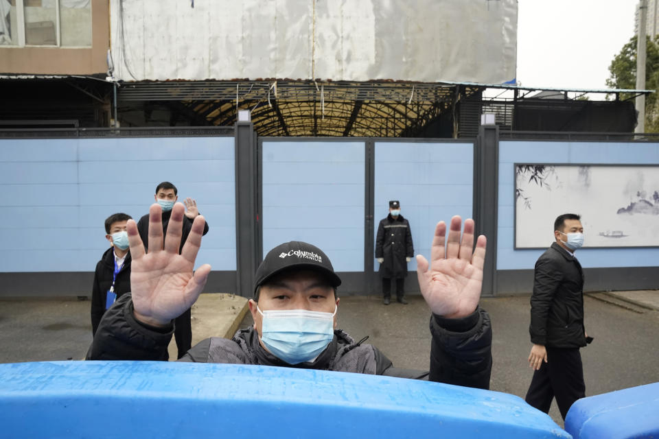 FILE - In this Jan. 31, 2021, file photo, a security guard waves for journalists to clear the road after a convoy carrying the World Health Organization team entered the Huanan Seafood Market on the third day of a field visit in Wuhan in central China's Hubei province. A member of the expert team investigating the origins of the coronavirus in Wuhan says the Chinese side granted full access to all sites and personnel they requested to visit and meet with. (AP Photo/Ng Han Guan, File)