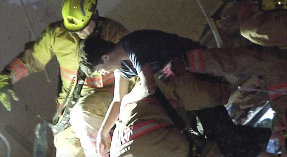This photo taken from video provided by ReliableNewsMedia firefighters rescue a survivor from the rubble of the Champlain Towers South Condo after the multistory building partially collapsed in Surfside, Fla., early Thursday, June 24, 2021. (ReliableNewsMedia via AP).