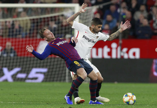 Sevilla's Banega, right, fight for the ball with FC Barcelona's Arthur Melo, during a Spanish Copa del Rey soccer match between Sevilla and FC Barcelona at the Ramon Sanche Pizjuan stadium in Seville, Spain, Wednesday Jan. 23, 2019. (AP Photo/Miguel Morenatti)
