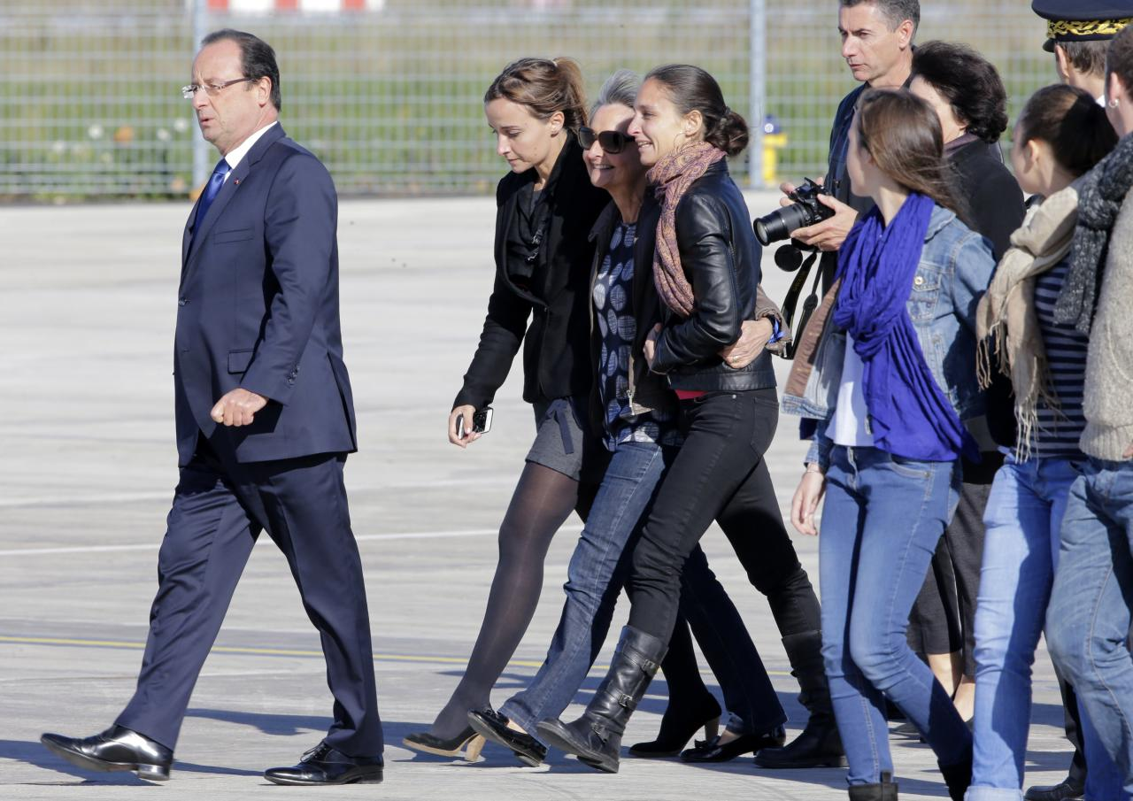 French President Francois Hollande (L) walks on the tarmac with relatives of former hostages Pierre Legrand, Daniel Larribe, Thierry Dol and Marc Feret upon their arrival at Villacoublay military airport, near Paris, October 30, 2013. Four Frenchmen held hostage in the Sahara desert by al Qaeda-linked gunmen for three years left Niger on a French government plane on Wednesday morning. The men, who were kidnapped in 2010 while working for French nuclear group Areva and a subsidiary of construction group Vinci in northern Niger, were freed on Tuesday after secret talks. REUTERS/Jacky Naegelen (FRANCE - Tags: POLITICS)
