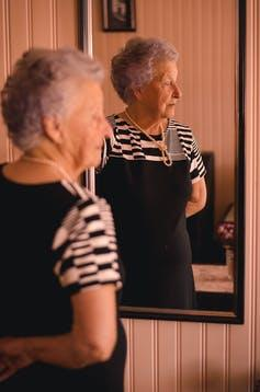 A woman with gray hair in a black dress and pearls stands in front of a mirror, looking off to one side.