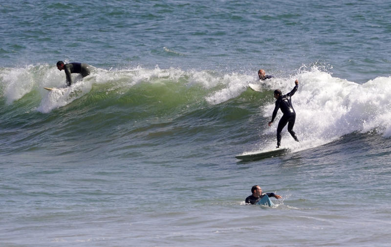 Surfers ride waves at County Line Beach during the coronavirus outbreak, Thursday, April 2, 2020, in Malibu, Calif. The new coronavirus causes mild or moderate symptoms for most people, but for some, especially older adults and people with existing health problems, it can cause more severe illness or death. (AP Photo/Mark J. Terrill)