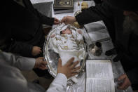 """Yaakov Tabersky, lest, presented his firstborn son, Yossef on a silver platter to Jewish priests from the Lelov Hassidic dynasty, during the """"Pidyon Haben"""" ceremony in Beit Shemesh, Israel, Thursday, Sept. 16, 2021. The Pidyon Haben, or redemption of the firstborn son, is a Jewish ceremony hearkening back to the biblical exodus from Egypt. (AP Photo/Oded Balilty)"""