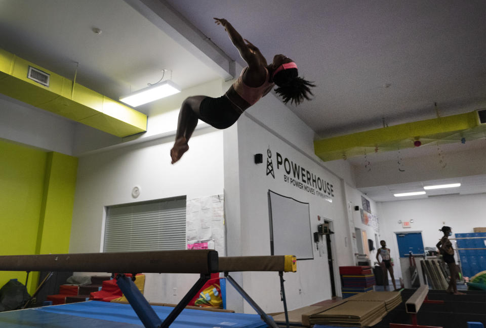 A young athlete flips off the balance beam at Power Moves Gymnastics and Fitness, Thursday, July 22, 2021, in Cedarhurst, N.Y. There's a phenomenon that happens every time Simone Biles appears on a screen inside Power Moves Gymnastics & Fitness. As if flipping a switch, the young women of color on the gym's competitive team spring to life, fueled by the jolt of adrenaline that comes watching the reigning Olympic champion test the limits of their sport. (AP Photo/Mark Lennihan)
