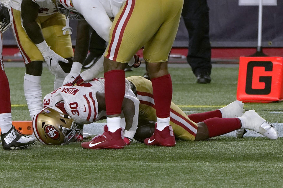 San Francisco 49ers running back Jeff Wilson Jr. lies on the turf after an injury while scoring a touchdown in the second half of an NFL football game against the New England Patriots Sunday, Oct. 25, 2020, in Foxborough, Mass. (AP Photo/Steven Senne)