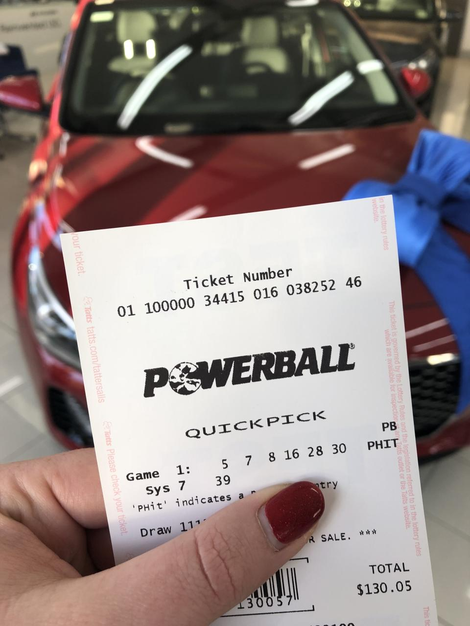 A woman holds a Powerball ticket in front of a red car.