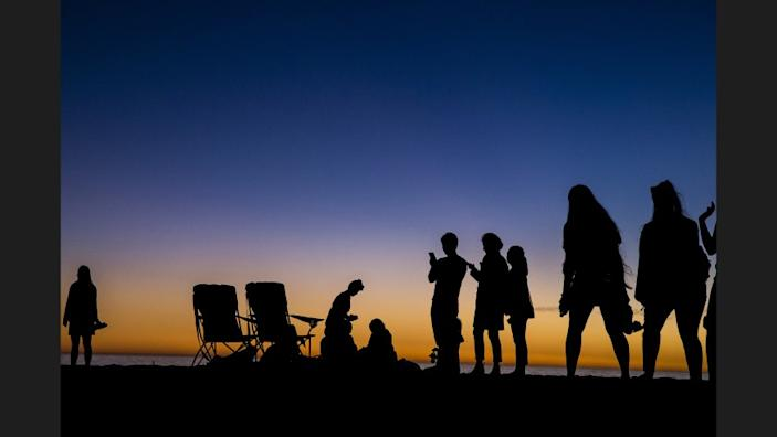 Beachgoers are cast in silhouette after the last rays of sunlight escape into the night on Santa Monica Beach on Wednesday.