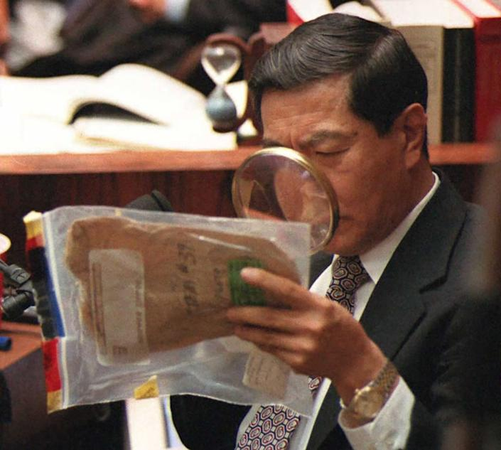 """<div class=""""inline-image__caption""""><p>Forensic scientist Dr. Henry Lee uses a magnifying glass to look at blood stains on an envelope used to collect the eyeglasses found at the Bundy crime scene during Hank Goldberg's cross-examination of Lee in the O.J. Simpson murder trial.</p></div> <div class=""""inline-image__credit"""">Getty</div>"""