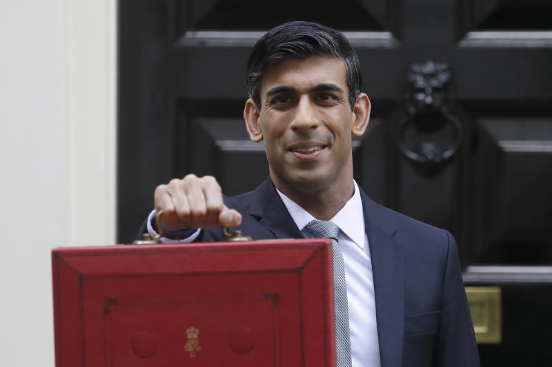 Britain's Chancellor of the Exchequer Rishi Sunak stands outside No 11 Downing Street and holds up the traditional red box that contains the budget speech for the media, he will then leave to make budget speech to House of Commons, in London, Wednesday, March 11, 2020. Britain's Chancellor of the Exchequer Rishi Sunak will announce the first budget since Britain left the European Union. (AP Photo/Kirsty Wigglesworth)