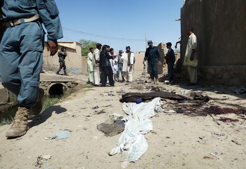 Afghans stand near human remains at the scene after an explosion in Kandahar, south of Kabul, Afghanistan, Monday, July 9, 2012. Three suicide bombers riding in a three-wheeled vehicle blew themselves up Monday afternoon in Kandahar city, killing two children and wounding several other civilians, said Kandahar provincial spokesman Ahmad Jawed Faisal. He said authorities had not determined the target of the explosion. (AP Photo/Allauddin Khan)
