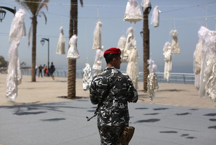 A Lebanese policeman guards an installation of wedding dresses by Lebanese artist Mireille Honein at Beirut's Corniche as ABAAD NGO ramps up pressure on Lebanon's reviled rape law (AFP Photo/PATRICK BAZ)