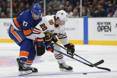 Jan 3, 2019; Uniondale, NY, USA; Chicago Blackhawks left wing Brandon Saad (20) plays the puck against New York Islanders left wing Anders Lee (27) during the third period at Nassau Veterans Memorial Coliseum. Mandatory Credit: Brad Penner-USA TODAY Sports