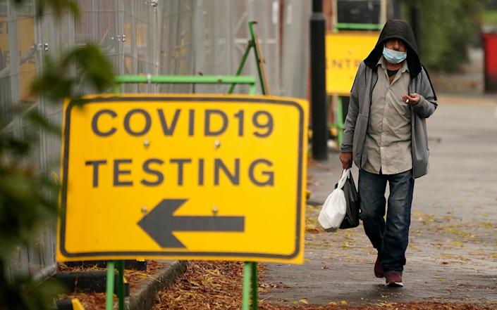 A man walks past a Covid-19 testing site on October 21, 2020 in Sheffield, England. - Christopher Furlong/Getty Images