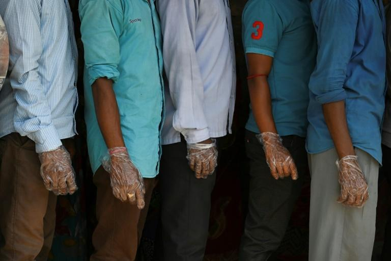 Voters wearing plastic gloves stand in a line to cast their vote outside a polling station during Phase 2 of West Bengal's legislative election in Nandigram