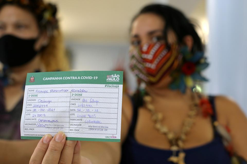 An Indigenous woman shows her vaccination card after receiving the second dose of Sinovac's CoronaVac coronavirus disease (COVID-19) vaccine at a health station, in Guarulhos, near Sao Paulo, Brazil March 2, 2021. REUTERS/Carla Carniel