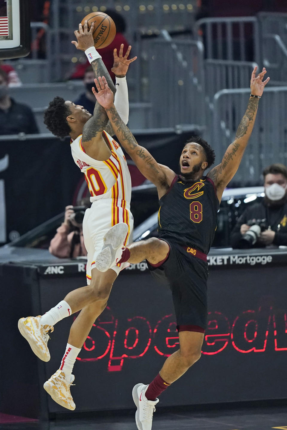 Cleveland Cavaliers' Lamar Stevens (8) and Atlanta Hawks' John Collins (20) battle for a loose ball in the first half of an NBA basketball game, Tuesday, Feb. 23, 2021, in Cleveland. Stevens was called for the foul. (AP Photo/Tony Dejak)