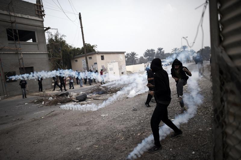 Bahraini protesters taking cover from tear gas during clashes with police following a demonstration in 2015 (AFP Photo/Mohamed al-Shaikh)