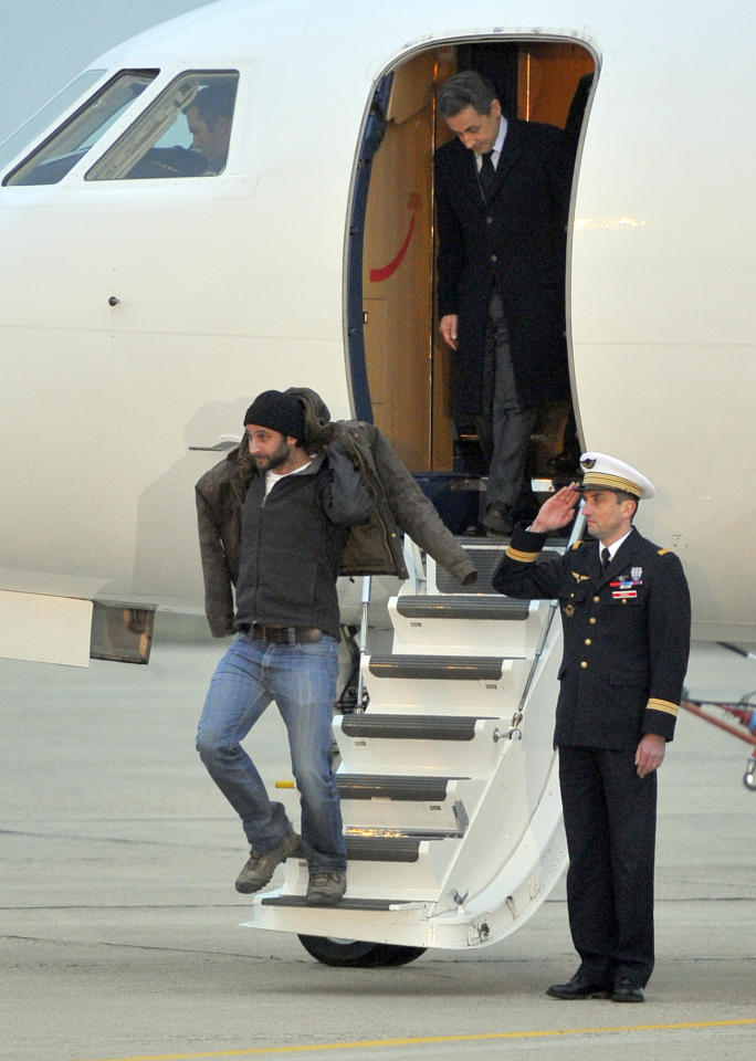 French photographer, William Daniels, bottom, followed by French President, Nicolas Sarkozy, alight from the plane carrying him and French reporter, Edith Bouvier, after they landed at the Villacoublay military airport, outside Paris, Friday, March 2nd, 2012. Two French journalists who were smuggled out of Syria have arrived in France. Edith Bouvier, who was injured, and William Daniels were caught up in a Syrian government siege of a rebel-held neighborhood in the city of Homs.(AP Photo/Zacharie Scheurer)