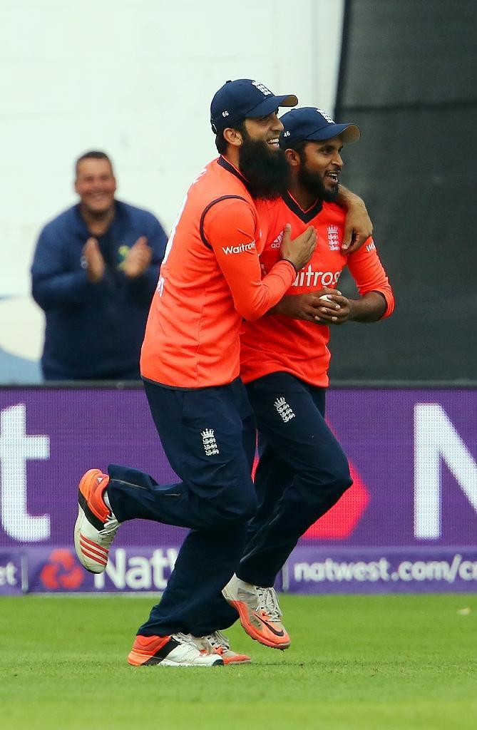 England's Moeen Ali (L) congratulates Adil Rashid after he takes the catch to dismiss Australia's Nathan Coulter-Nile during the Twenty20 International match in Cardiff on August 31, 2015 (AFP Photo/Geoff Caddick)