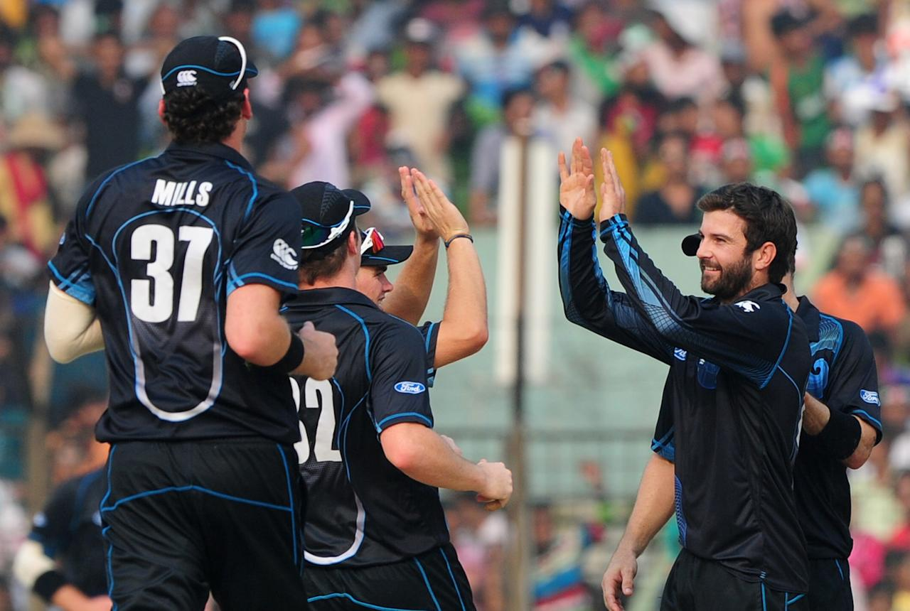New Zealand bowler Anton Devcich (R) celebrates teammates the dismissal of Bangladesh batsman Mominul Haque during the third One-Day International (ODI) cricket match between Bangladesh and New Zealand at Khan Jahan Ali Stadium in Fatullah on the outskirts of Dhaka on November 3, 2013.  AFP PHOTO/ Munir uz ZAMAN        (Photo credit should read MUNIR UZ ZAMAN/AFP/Getty Images)