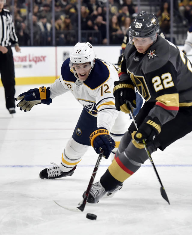 Buffalo Sabres center Tage Thompson (72) reaches for the puck against Vegas Golden Knights defenseman Nick Holden (22) during the first period of an NHL hockey game Tuesday, Oct. 16, 2018, in Las Vegas. (AP Photo/David Becker)