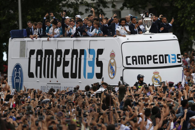 Real Madrid players wave to fans from the top of an open top bus in Cibeles square, in Madrid, Spain, Sunday, May 27, 2018, to celebrate winning the Champions League final against Liverpool. (AP Photo/Francisco Seco)