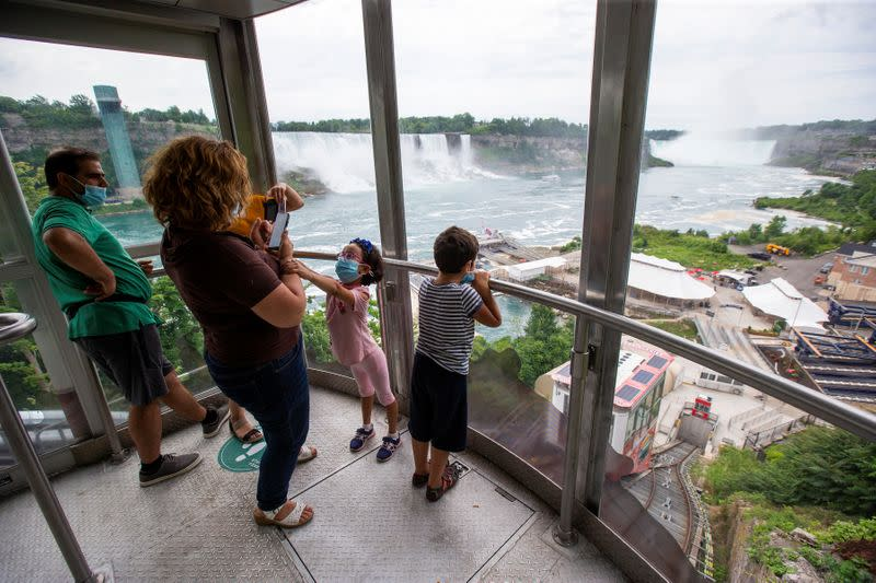 Canadian tourists take photos as they travel down to the Hornblower tourist boat, limited under Ontario's rules to just six passengers amid the spread of the coronavirus disease (COVID-19), in Niagara Falls