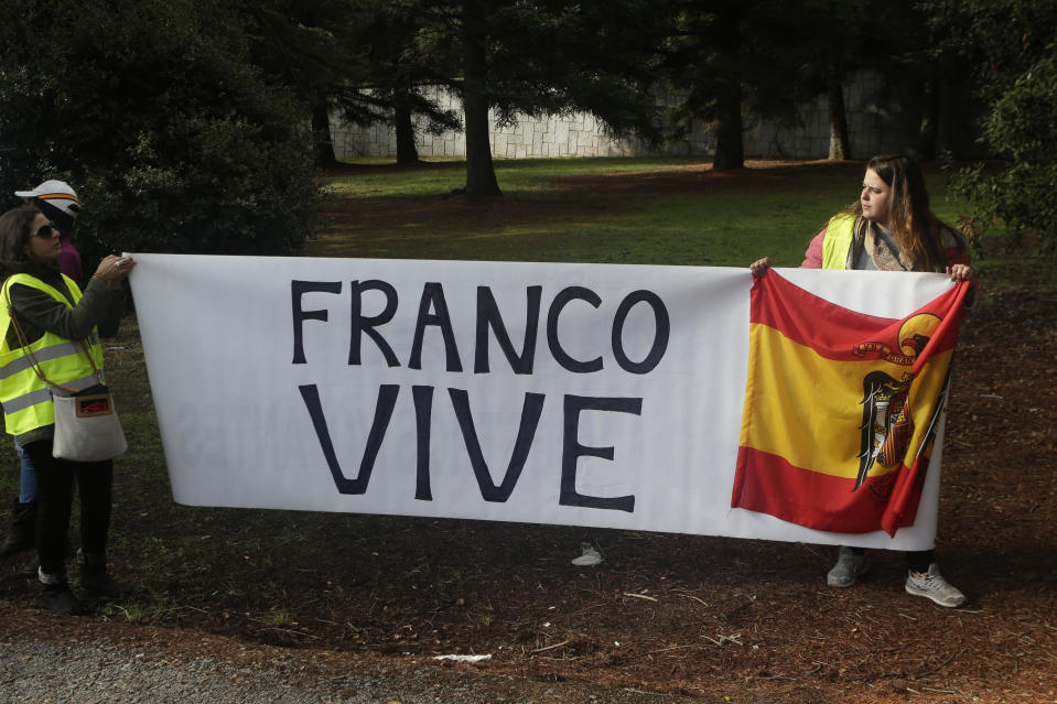 """People carrying a banner reading in Spanish """"Franco is alive"""" and holding a pre-constitutional Spanish flag stand outside the Fallen mausoleum near El Escorial, outskirts of Madrid, Thursday, Oct. 24, 2019. Forty-four years after his demise, the remains of Spanish dictator Gen. Francisco are to be dug out of his grandiose resting place outside Madrid and taken to a small family crypt, finally satisfying a long-standing demand of his victims' relatives and others who suffered under his regime. (AP Photo/Paul White)"""