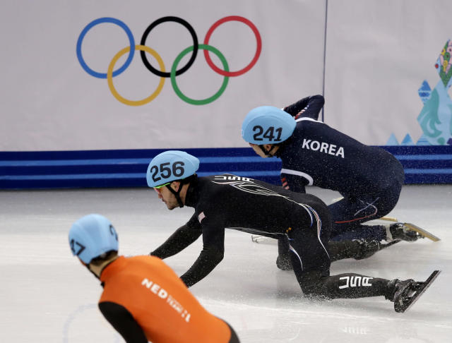 Lee Ho-suk of South Korea, right, and Eduardo Alvarez of the United States, centre, crash out in a men's 5000m short track speedskating relay semifinal at the Iceberg Skating Palace during the 2014 Winter Olympics, Thursday, Feb. 13, 2014, in Sochi, Russia. (AP Photo/Darron Cummings)
