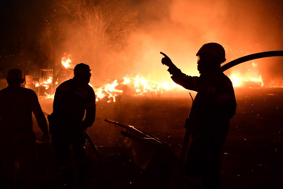 Fire burns a house in Adames area, in northern Athens, Greece, Tuesday, Aug. 3, 2021.Thousands of people fled their homes north of Athens on Tuesday as a wildfire broke out of the forest and reached residential areas. The hurried evacuations took place just as Greece grappled with its worst heat wave in decades. (AP Photo/Michael Varaklas)