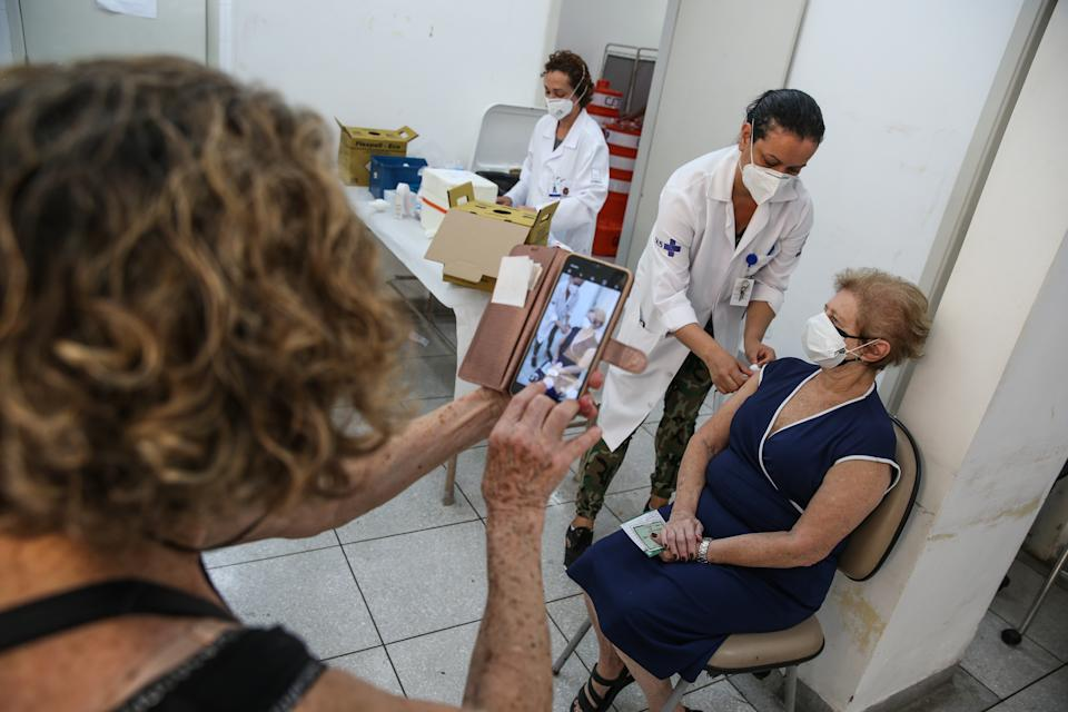 SAO PAULO, BRAZIL - MARCH 15: A senior citizen receives the coronavirus vaccination shot at a vaccination post in the Santa Cecilia Basic Health Unit on March 15, 2021 in Sao Paulo, Brazil. The state of Sao Paulo started to immunize citizens aged between 75 and 76 years old. Health authorities announced they expect to vaccinate 420,000 people within this phase and should reach the milestone of 4 million vaccinated people today. Brazil has over 11.400,000 confirmed positive cases of coronavirus and has over 278,000 deaths. (Photo by Alexandre Schneider/Getty Images)