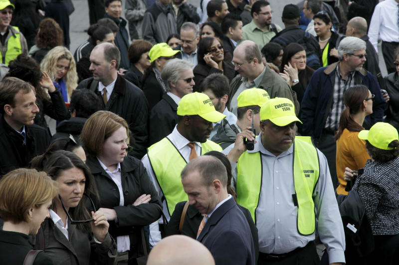 Members of the evacuation team stand among other office workers after Two World Financial Center was briefly evacuated in New York, Thursday, April 12, 2012. Authorities say an evacuation was ordered as a precaution at a World Financial Center building after a security guard reported a package that seemed suspicious. (AP Photo/Seth Wenig)