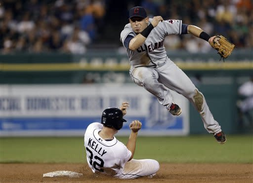Cleveland Indians shortstop Asdrubal Cabrera jumps away from Detroit Tigers' Don Kelly (32), while watching his throw to first to complete the double play on Alex Avila during the fifth inning of a baseball game in Detroit, Tuesday, Sept. 4, 2012. (AP Photo/Paul Sancya)