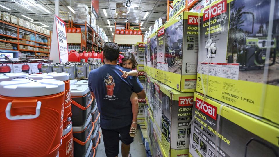 Frank Barakat carries his daughter Valentina, 2, through an shopping aisle dedicated for hurricane supplies as the Home Depot store prepares for possible effects of tropical storm Elsa in Miami on Saturday, July 3, 2021. Elsa fell back to tropical storm force as it brushed past Haiti and the Dominican Republic on Saturday and threatened to unleash flooding and landslides before taking aim at Cuba and Florida. (Al Diaz/Miami Herald via AP)