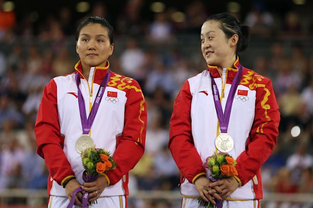 LONDON, ENGLAND - AUGUST 02: Silver medalists Jinjie Gong (L) and Shuang Guo of China celebrate with their silver medals during the medal ceremony for the Women's Team Sprint Track Cycling on Day 6 of the London 2012 Olympic Games at Velodrome on August 2, 2012 in London, England. (Photo by Bryn Lennon/Getty Images)