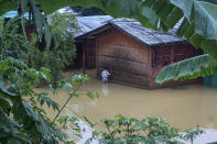 A Rohingya refugee walks through flood water following heavy rains at the Rohingya refugee camp in Kutupalong, Bangladesh, Wednesday, July 28, 2021. Days of heavy rains have brought thousands of shelters in various Rohingya refugee camps in Southern Bangladesh under water, rendering thousands of refugees homeless. (AP Photo/ Shafiqur Rahman)