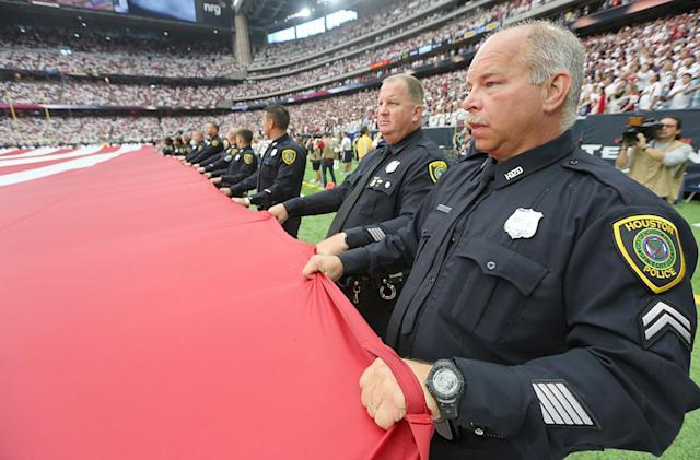 <p>Police officers hold a giant American flag before the Houston Texans play the Chicago Bears at NRG Stadium on September 11, 2016 in Houston, Texas. (Photo by Thomas B. Shea/Getty Images) </p>