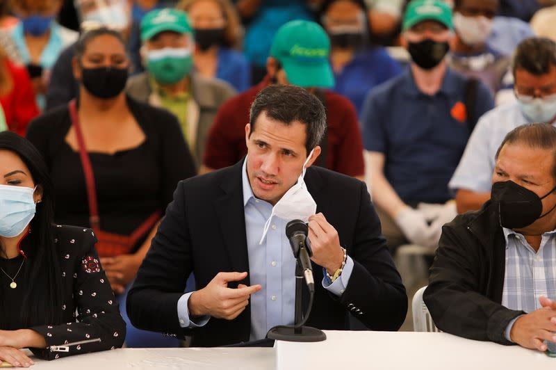 Venezuelan opposition leader Juan Guaido removes his face mask while arriving to a news conference in Caracas