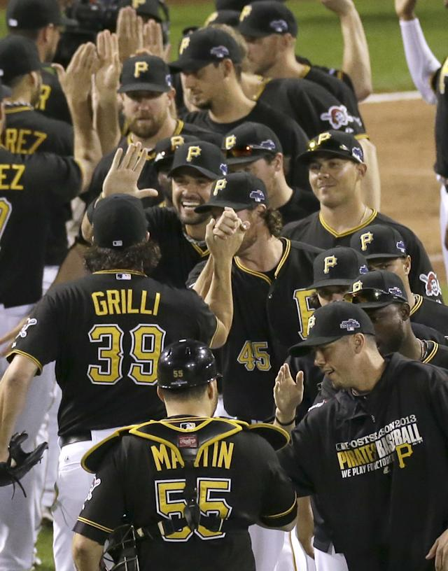 Pittsburgh Pirates' Russell Martin (55) and Jason Grilli celebrate with teammates after their 5-3 game 3 win over the St. Louis Cardinals in a National League baseball division series on Sunday, Oct. 6, 2013, in Pittsburgh. (AP Photo/Tom Puskar)