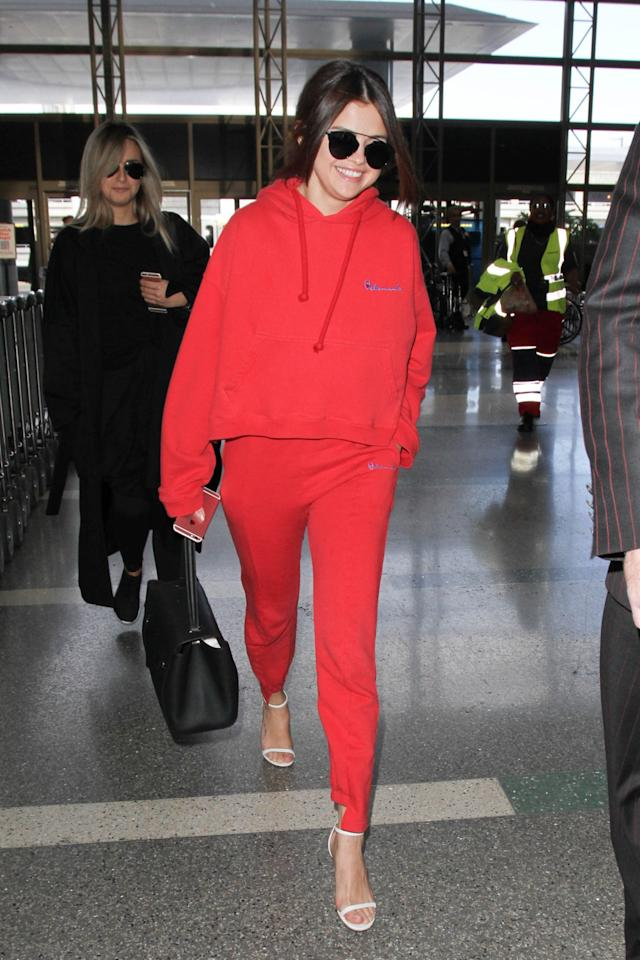 <p>Gomez opts for a matching red hoodie and fleece pants from Vetements. (Photo: Getty) </p>