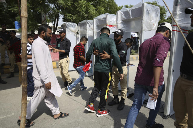 Pakistani police officers search spectators outside the National stadium in Karachi, Pakistan, Monday, Sept. 30, 2019. Karachi's 10-year long wait to host a one-day international finally ended on Monday as Pakistan won the toss and elected to bat against Sri Lanka in the second ODI. (AP Photo/Fareed Khan)