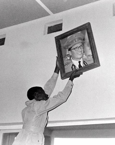 FILE - In this July 22, 1960 file photo, an unidentified Congolese citizen removes a portrait of Belgium's King Baudouin, at the N'Djili Airport in Leopoldville, the capital before it was later renamed in 1966 to Kinshasa, in Congo. On Tuesday, June 30, 2020 Congo is marking the 60th anniversary of achieving independence from the colonial rule of Belgium. (AP Photo, File)