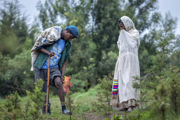 Militia fighter Abebaw Adugna, left, shows his wound to a woman from his hometown of Addi Arkay at a center for the internally-displaced in Debark, in the Amhara region of northern Ethiopia Friday, Aug. 27, 2021. Adugna was shot by Tigrayan forces during a fight for his town and the bullet is still in his leg. As they bring war to other parts of Ethiopia such as the Amhara region, resurgent Tigray fighters face growing allegations that they are retaliating for the abuses their people suffered back home, sending hundreds of thousands of people fleeing in the past two months. (AP Photo/Mulugeta Ayene)