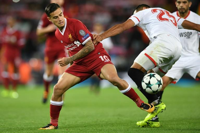 Liverpool midfielder Philippe Coutinho (L) vies with Sevilla defender Gabriel Mercado during the UEFA Champions League Group E football match between Liverpool and Sevilla at Anfield in Liverpool, north-west England on September 13, 2017