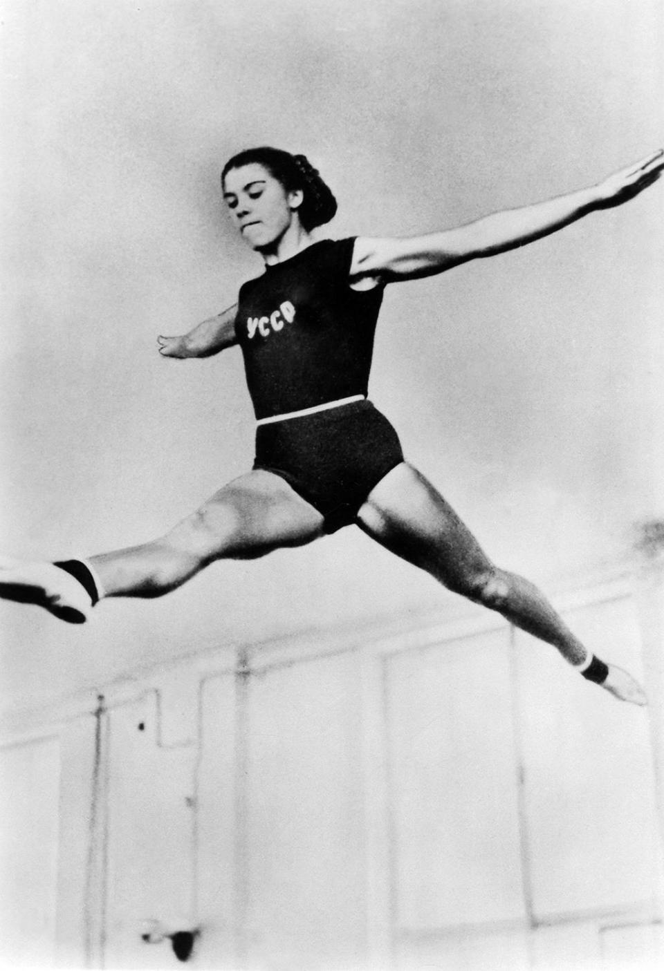 <p>Larisa Latynina performs at the 1956 Melbourne Olympics. (Photo by ullstein bild/ullstein bild via Getty Images) </p>