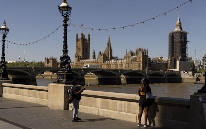 Pedestrians walk along the River Thames in view of The Houses of Parliament in London - Jason Alden/Bloomberg