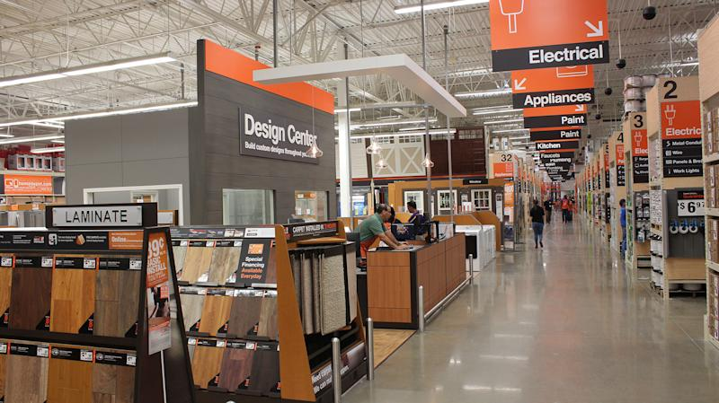 Inside of Home Depot store looking at aisle markers and laminate flooring.