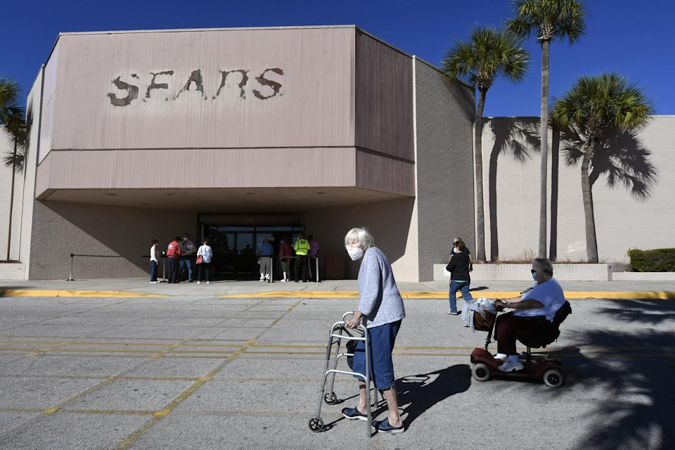 People are seen outside a walk-in COVID-19 vaccination POD inside a vacant Sears store at the Lake Square Mall in Leesburg, Florida. The appointment-only site for frontline health care workers and seniors 65 and older is vaccinating around 700 people a day. (Photo by Paul Hennessy/SOPA Images/LightRocket via Getty Images)
